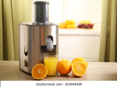 Juicer and orange juice on kitchen table