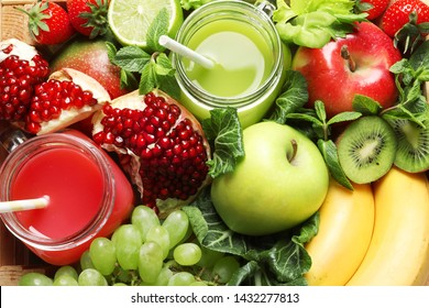 Juices in mason jars with fresh fruits in wooden crate