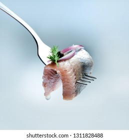 A juicy and appetizing piece of herring on a fork, decorated with red onions, sweet peas and a sprig of dill. A drop of oil is flowing.