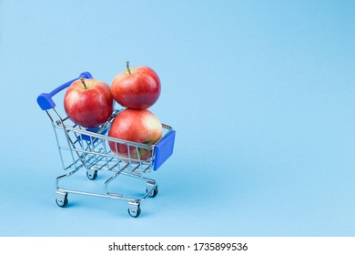 Juicy apples in a shopping basket on a blue background. The concept of a fresh sale. Copy space.