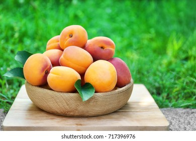 Juicy apricots in bowl on stand outdoor