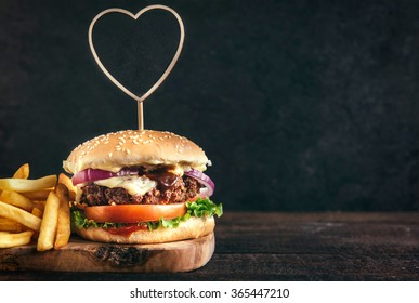 Juicy beef burger and french fries on wooden board with blank space,selective focus