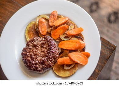 Juicy beef burger with potato carrots and onion garnish on the rustic background