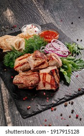 Juicy beef shish kebab with sauce, potatoes, pita bread and herbs. Photo from above