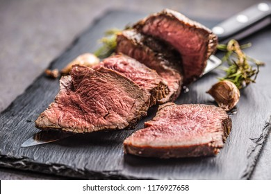 Juicy beef steak with spices and herbs on cutting board.