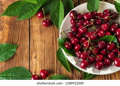 Juicy berries of sweet cherry with leaves on a wooden table. Top view with copy space