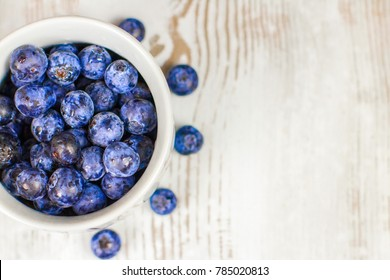 Juicy blueberries in a small white jar with scattered blueberries on the wooden table.
