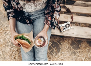 juicy burger and lemonade in hands, top view. stylish hipster woman holding  cheeseburger and refreshing drink. boho girl at street food festival. summer vacation picnic. space for text
