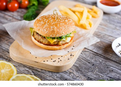 Juicy burgers with ingredients: salad, mushrooms, onion, beef, pepper and tomato sauce over wooden table. Black background and copy space.