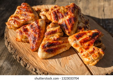 Juicy chicken wings barbecue. Grilled chicken. Tasty food. Food on a wooden stand.