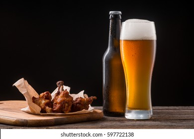 Juicy chicken wings under sauce for beer. Lager ale tastes well with any kind of meat. Studio shot made in pub.