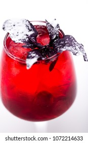 juicy cocktail with cherry at wineglass on white background