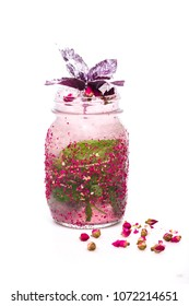 juicy cocktail at jar decorated with rose and basil on white background