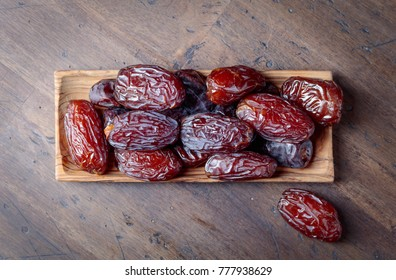 Juicy dates in a bowl on a old wooden table . Top view .
