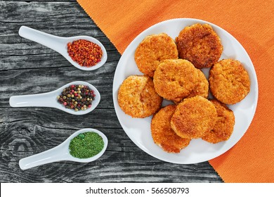 juicy delicious  coated with breadcrumbs and then fried chicken cutlets on white dish with spices in porcelain spoons on old dark wooden boards, view from above