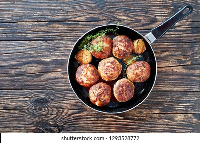 juicy delicious homemade fried turkey, chicken cutlets, patties of chopped meat in a skillet with thyme, garlic and onion on an old wooden table, view from above, flatlay