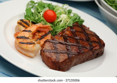 Juicy delicious sirloin steak with grilled shrimps - Surf and Turf
