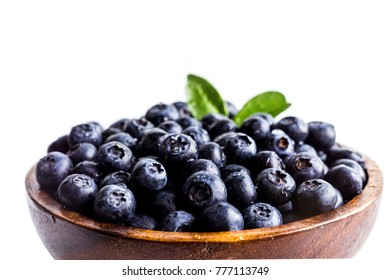 Juicy and fresh blueberries with green leaves on wooden bowl. Healthy eating