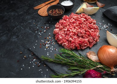 Juicy, fresh minced meat with spices on a flat plate on a black background. Side view, horizontal.