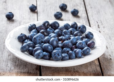 juicy fresh organic blueberries in a plate on a wooden table