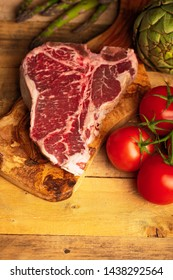 Juicy fresh piece of marbled beef steak with vegetables for grilling. Culinary background, recipe book, taste food, Steak cooking. With space, vertical photo