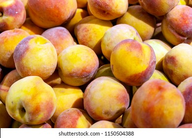 Juicy fruits of peach nectarines are spread out in even rows in the shop window.