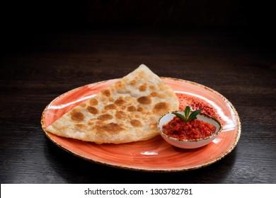 Juicy golden hot cheburek with adjika sauce on a plate in a Georgian restaurant. National oriental flour dish.