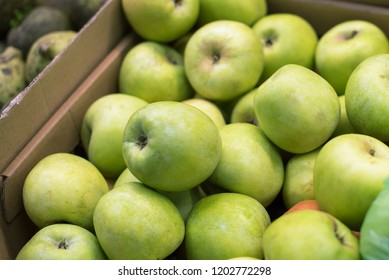 juicy green apples in a carton box are sold at the fruit shop. delicious ripe fruit. vegetable shop