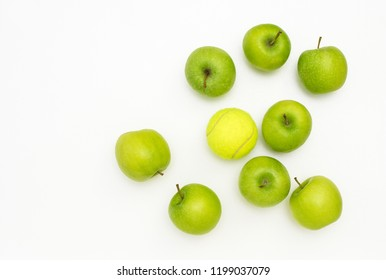 Juicy green apples lying on white background but one is different, the odd one out, an outsider, different and unlike the others because it is a tennis ball, concept of misfit