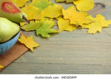 juicy green pears in a bowl and autumn leaves on brown wooden background