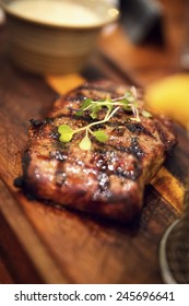 Juicy grilled beef steak on a wooden plate