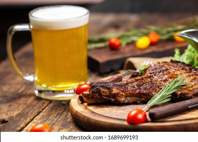 Juicy grilled meat on a wooden board with vegetables, herbs and a beer, side view, horizontal, closeup