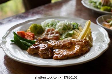 juicy grilled pork chop with greens