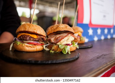 juicy hamburgers with cutlet, with bacon on a wooden table. street food. Bright juicy appetizing burgers with a cutlet, cheese, marinated cucumbers, tomatoes and bacon. Space for text