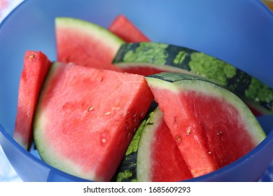 Juicy, healthy and fresh watermelon slices in a blue plastic bowl. Watermelon is a red and green fruit full of water and vitamins, perfect snack for summertime for the ones with a healthy lifestyle.