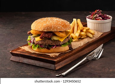 Juicy homemade cheeseburger with onion rings and dried tomatoes. Beef Burger with Cheese and Salad