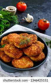 Juicy homemade cutlets (beef, pork, chicken) on a black background.