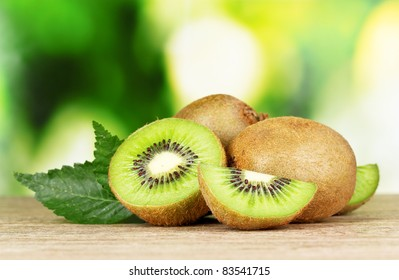 Juicy kiwi fruit on wooden table on green background