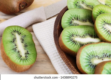 juicy kiwi slices on a wooden plate on the table close-up, delicious fruit wood, dietary products, healthy ingredients, tropical fruits close-up cut into pieces and served