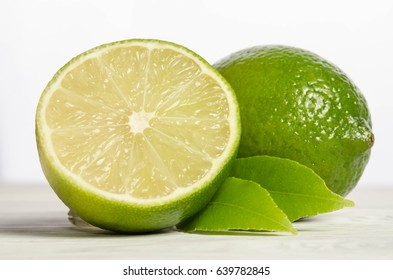 Juicy lime with its leaves on white wooden background