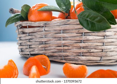 Juicy mandarins with green leaves. Full basket of mandarin on a white background.
