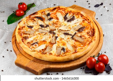 juicy meat pizza with chicken and beef on a wooden tray decorated with pepper and tomatoes on a paper lining