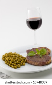 Juicy meat served with peas and basil and red wine glass.