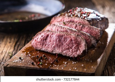 Juicy medium Beef Rib Eye steak slices in pan on wooden board with fork and knife herbs spices and salt.