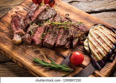 Juicy medium rare beef steak on wooden board with herbs.