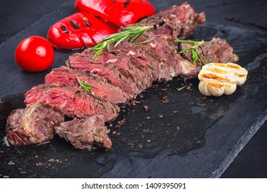 Juicy medium rare beef steak slices on ceramic board with herbs spices and salt.