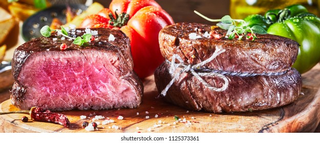 Juicy medium rare fillet steak mignon with one of the medallions cut through to show the texture of the lean healthy meat on a wooden chopping board with tomatoes
