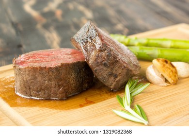 Juicy medium roast steak on wooden deck with grilled garlic, rosemary and green aspargus