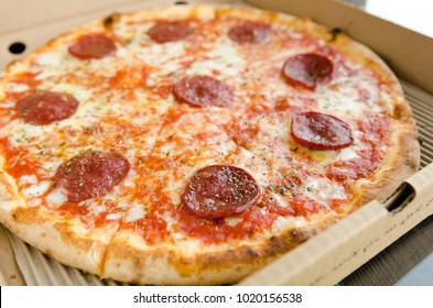 Juicy pepperoni pizza with melted mozzarella cheese and oregano sprinkle, served in a takeaway box