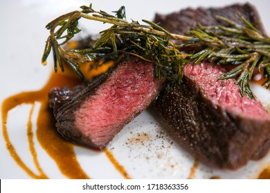A juicy piece of rare beef steak with brown sauce and garnished with rosemary